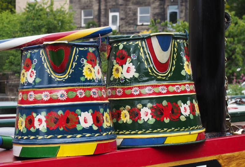 Typical traditional british painted canal boat pails used on narrowboats with a roses pattern. 19th century typical traditional british painted canal boat pails stock images