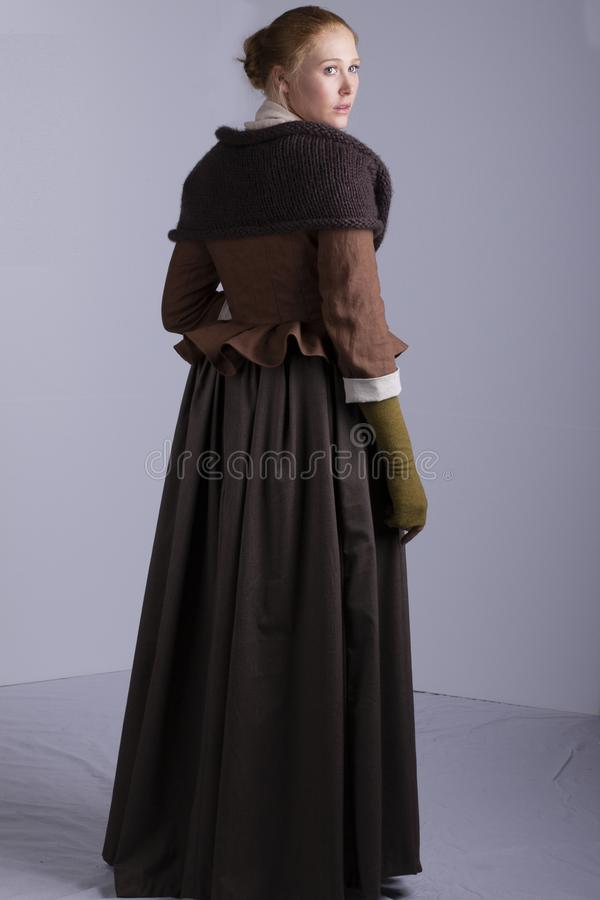 18th century woman in brown outfit on plain studio backdrop royalty free stock image