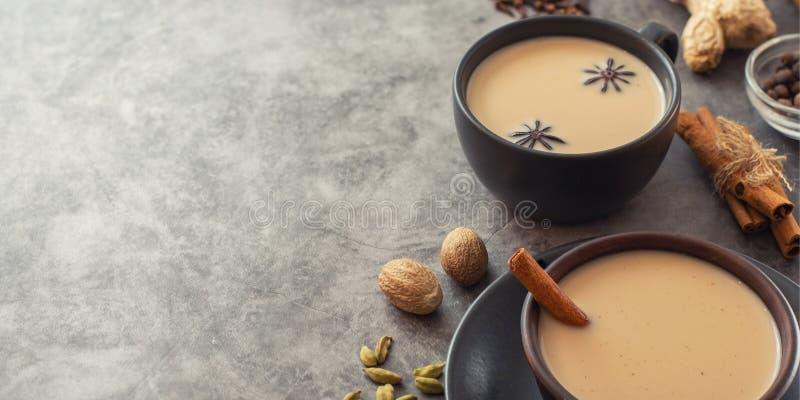 Th? de Masala Indien traditionnel Chai dans la tasse noire avec épicé sur le fond gris Avec l'espace de copie photo stock