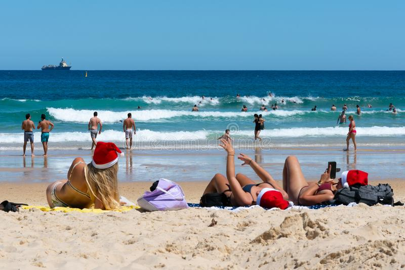 Three young ladies wearing Christmas hat on Christmas eve on Bondi beach Sydney Australia stock image