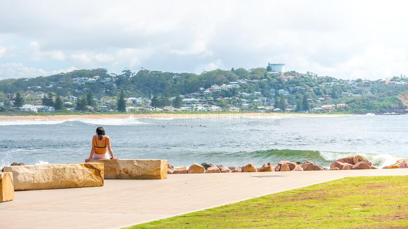 20th Feb 2020 - Avoca Beach NSW, Australia : woman sitting at the beach looking at the view. Outdoors lifestyle travel concept editorial image royalty free stock images