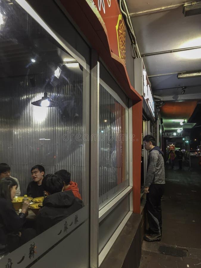 24th Februari 2109 - asiatisk man som ser in i ett restaurangexponeringsglasfönster arkivbild