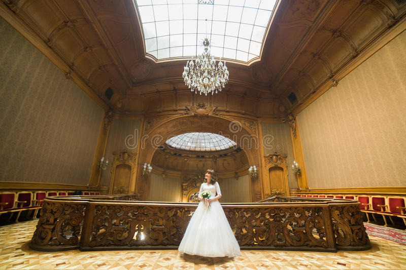 Th horiontal photo of the beautiful bride with the wedding bouquet spending time in the antient baroque palace. stock images