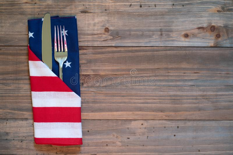 4th of July Rustic Picnic Table Place Setting with silverware and American Flag napkin with background of wood boards for copy spa. Ce stock image