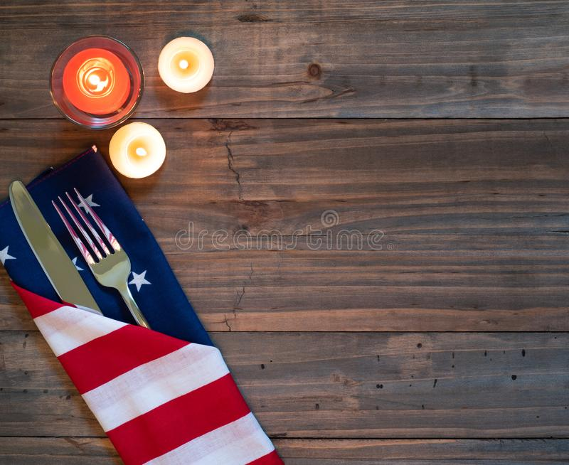 4th of July Rustic Table Placesetting with American flag napkin, silverware and three candles on a wood boards background with roo. M or space for copy, text or royalty free stock images