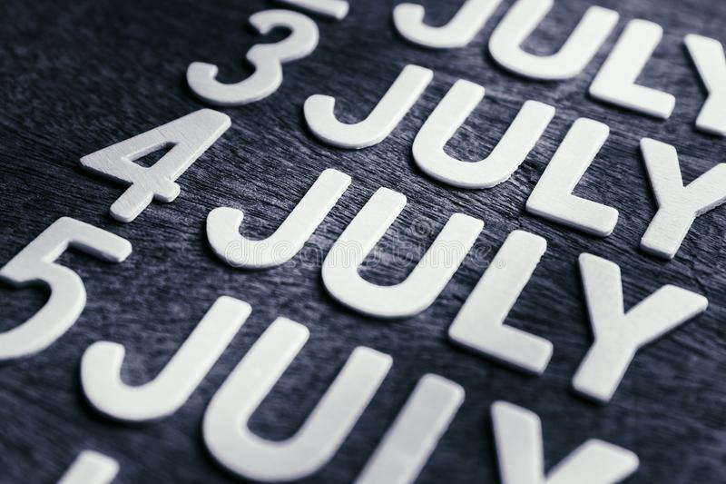 4th of July Wood Letters. In running date of July month on wood background stock photo