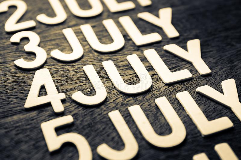 4th of July Wood Letters. In running date of July month on wood background royalty free stock photography