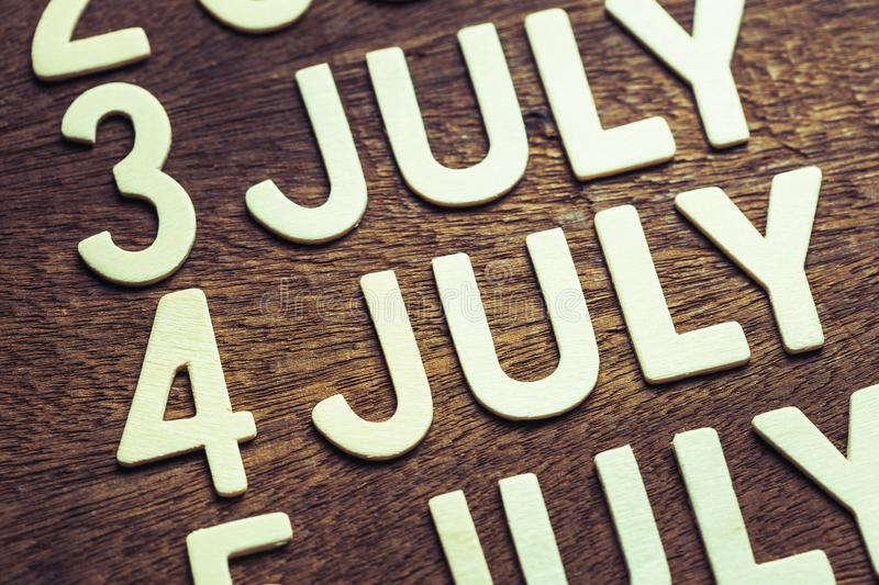4th of July Wood Letters. In running date of July month on wood background stock photos