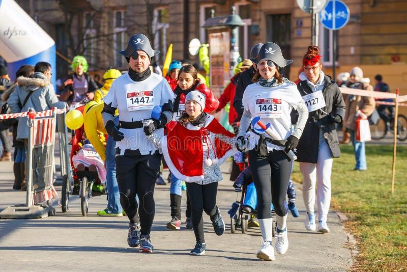 12th nytt års Eve Race i Krakow Folket som kör iklädda roliga dräkter arkivbild