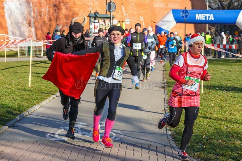 12th nytt års Eve Race i Krakow Folket som kör iklädda roliga dräkter royaltyfri fotografi