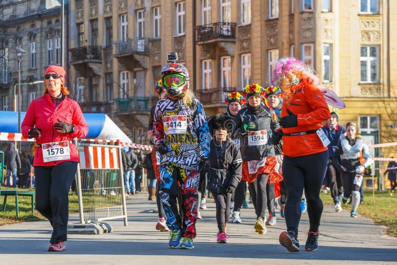 12th nytt års Eve Race i Krakow Folket som kör iklädda roliga dräkter arkivfoto