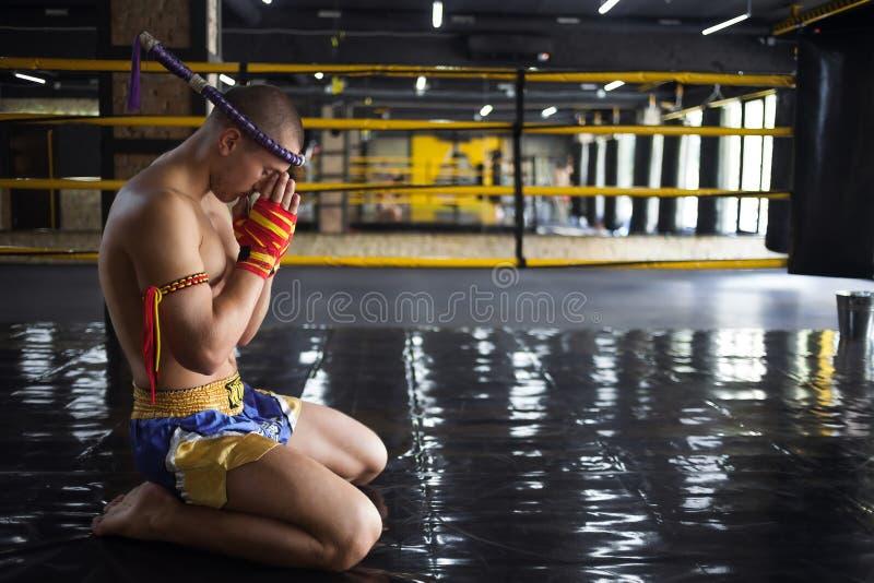 Thaïlandais de Muay de combattant cintré dans l'anneau image stock