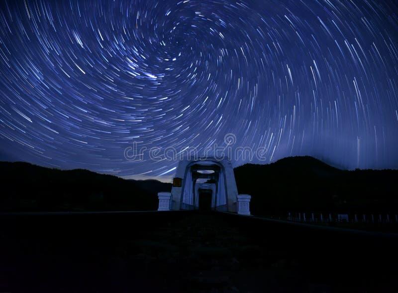Tha Chomphu铁路桥在天空的一串漩涡螺旋星足迹 免版税图库摄影