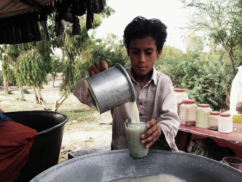 Thadal Seller. A poor child sold the thadal drink for the survival of a life. thadal is a drink which made up of Almond, White Poppy Seeds and Sugar etc. it is stock photos
