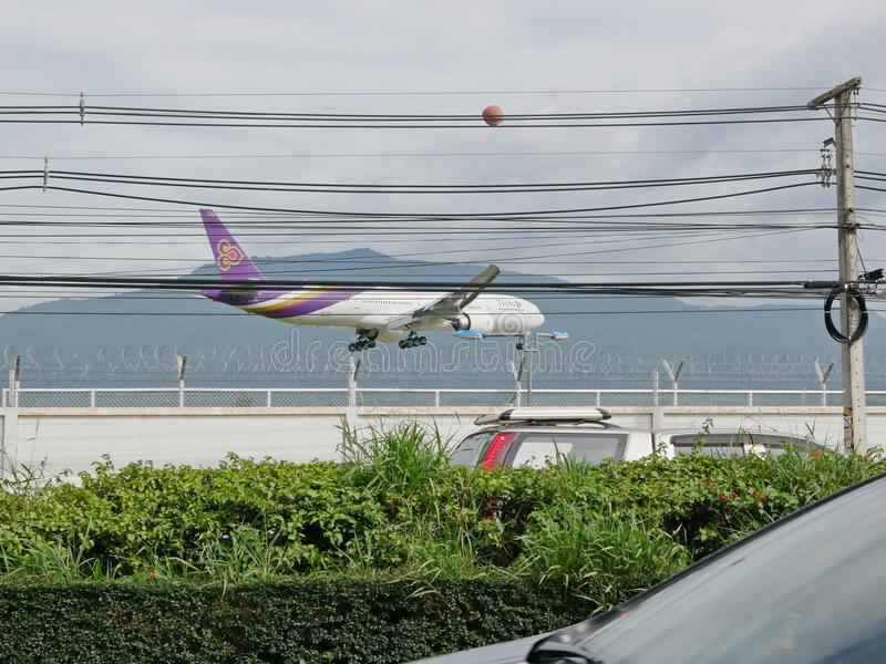 Thai Airway airplane is landing at Chiang Mai International Airport, Chiang Mai, Thailand, flying low above the street with traffi. Muang, Chiang Mai / Thailand royalty free stock photography