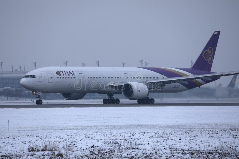 Thai Airways taxiing in Munich Airport, MUC, snow on runway. Thai Airways doing taxi in Munich Airport, MUC, snow in winter royalty free stock photos