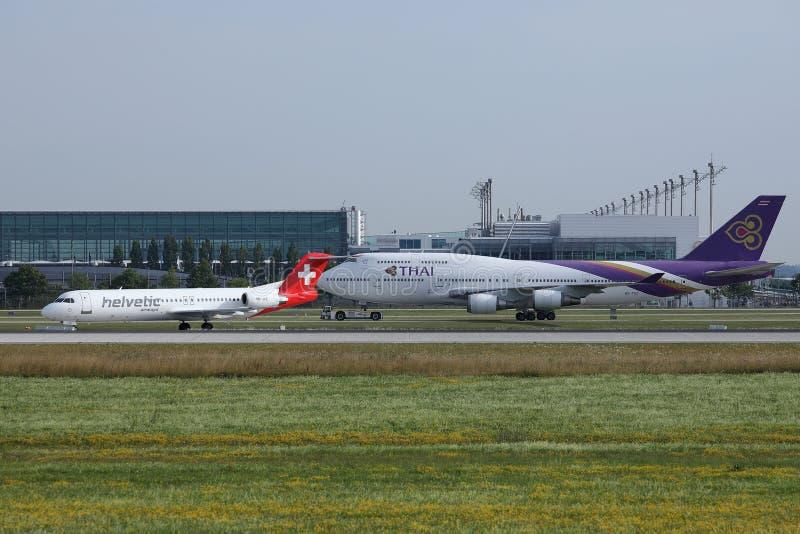 Thai Airways et Helvetic roulant au sol dans l'aéroport de Munich, MUC, vue de face photo stock