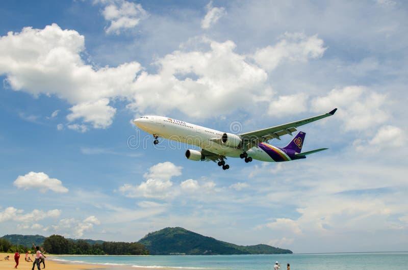 Thai Airways flygplanlandning på Phuket den internationella flygplatsen royaltyfri fotografi
