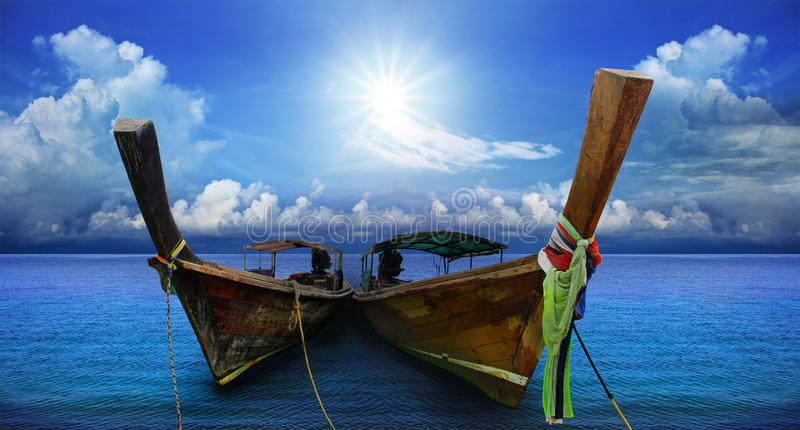 Thai andaman long tailed boat southern of thailand on sea beach. With beautiful sun shining over sky stock photo