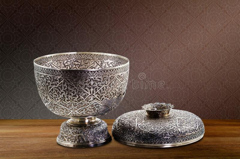 Thai antique ancient grunge silver bowl on wooden tabletop on vintage brown purple concrete wall background stock photos