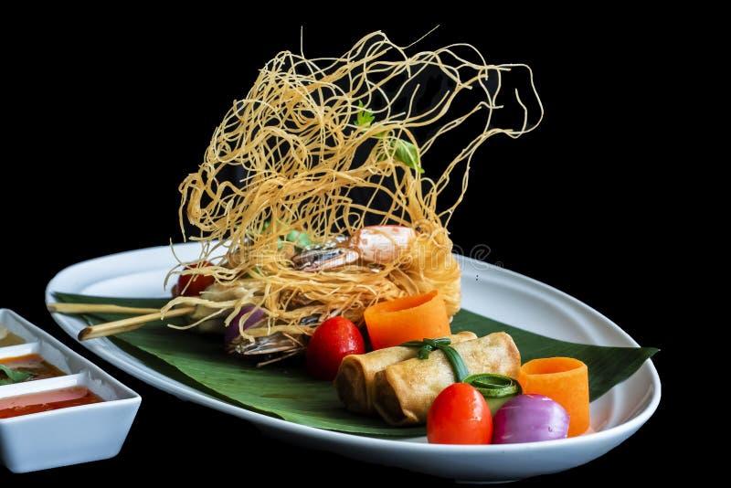 Thai appetizers spring rolls, crispy prawn, Thai sausage, chicken satay on black background. Thai appetizers spring rolls crispy prawn Thai sausage chicken stock image