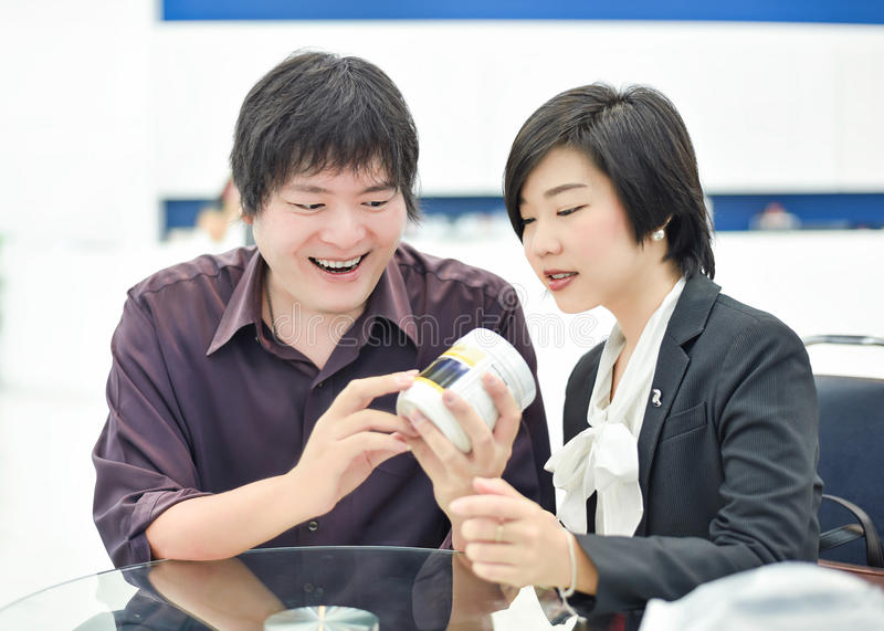 Thai (Asian) business copule are showing glad expression in their product design stock image