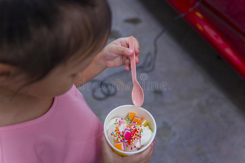 Thai/Asian cute little kids eating Ice cream in a cup or mango bar/candy. High resolution image gallery stock photo
