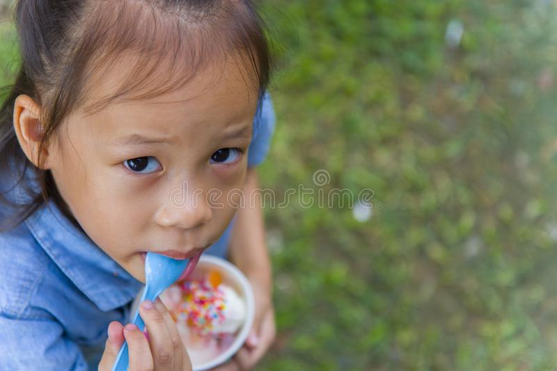 Thai/Asian cute little kids eating Ice cream in a cup or mango bar/candy. High resolution image gallery royalty free stock photography