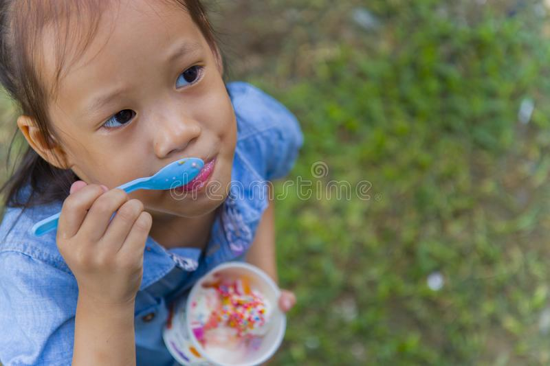 Thai/Asian cute little kids eating Ice cream in a cup or mango bar/candy. High resolution image gallery stock photos