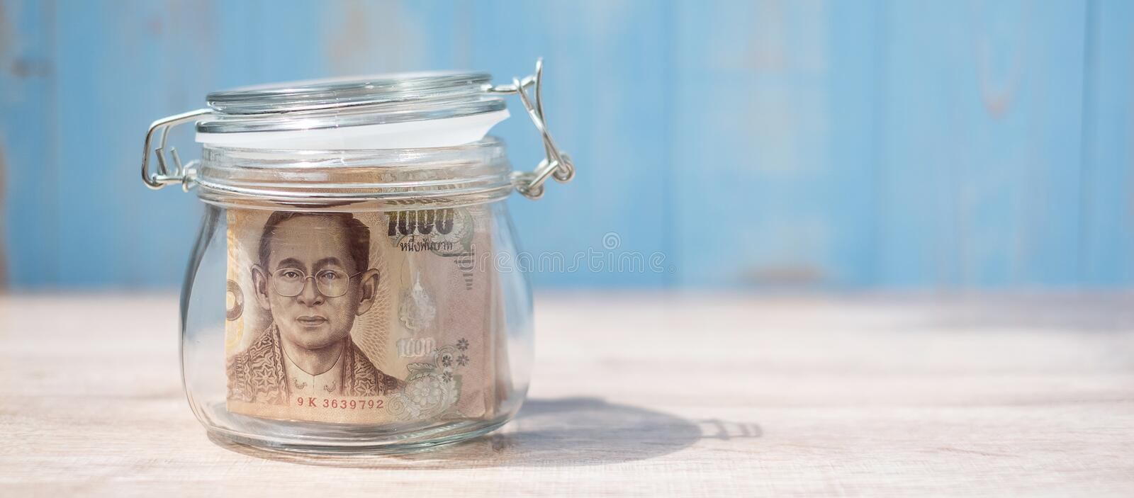 1000 Thai Baht banknote in glass jar. Money, business, investment, retirement planning, finance and world Saving day concepts royalty free stock photo