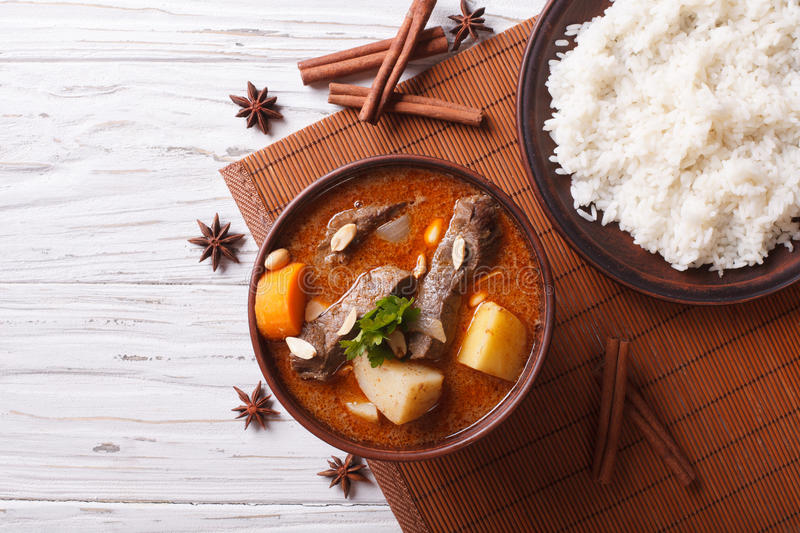 Thai beef massaman curry and rice side dish. horizontal top view. Hot traditional Thai beef massaman curry with peanuts and rice side dish. horizontal view from stock image