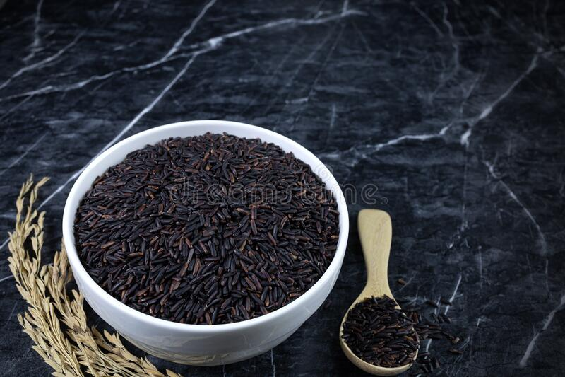 Thai black rice, rice berry  in white ceramic bowl and wooden spoon on dark marble table.  stock photo