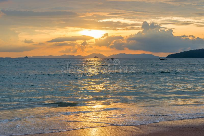 Thai boats in the sea against the setting sun. A photo in orange tones royalty free stock photo