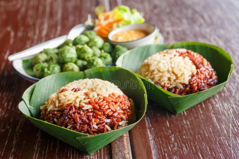 Thai Brown Rice Meal. Organic steamed brown rice in banana leaves dish, traditional Thai meal stock photo