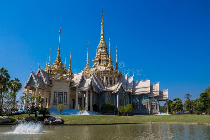 Thai buddhist temple wat near the pond. Thai buddhist temple wat in Thailand beautiful decorated with high towers. Pagoda with rich decoration stock photography