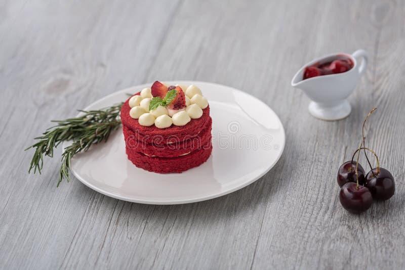 thai cake Röd kaka för sammet Kakor dekorerade med den röda kakan på den trätabellen och blomman jordgubbar som moring Körsbär i  royaltyfri foto
