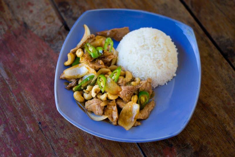 Thai cashew nut pork Kradan. Fresh prepared asian spicy cashew nut pork, onion and pepper stirfry served with jasmine rice in local restaurant on Koh Kradan stock photo