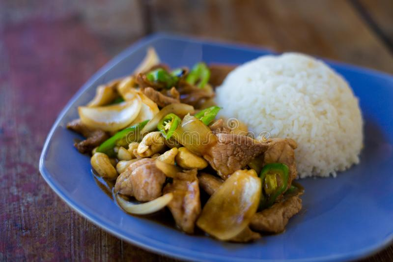 Thai cashew nut pork Kradan. Fresh prepared asian spicy cashew nut pork, onion and pepper stirfry served with jasmine rice in local restaurant on Koh Kradan stock photography