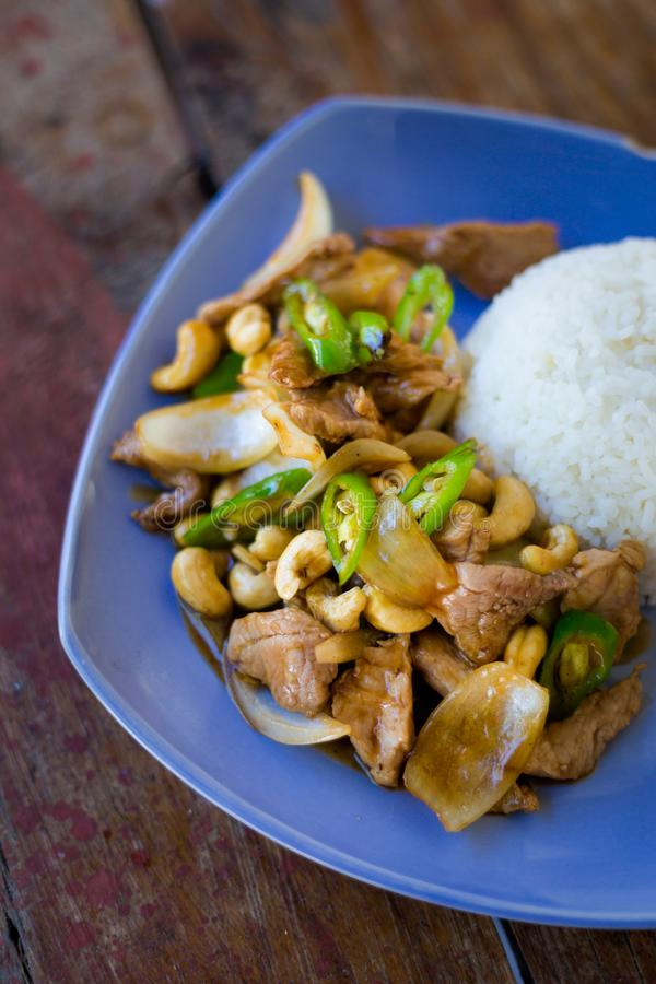 Thai cashew nut pork Kradan. Fresh prepared asian spicy cashew nut pork, onion and pepper stirfry served with jasmine rice in local restaurant on Koh Kradan royalty free stock image