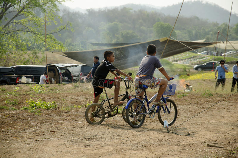Thai children biking bicycle at Sritasala Cemetery Chinese grave stock image