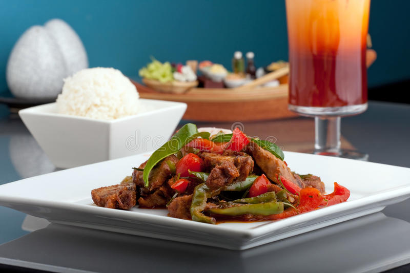 Thai Chile Basil Duck. A fresh dish of Thai style roast chile basil duck with mixed vegetables white jasmine sticky rice and thai iced tea stock photography