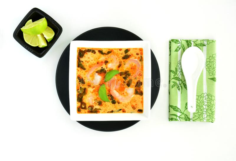 Thai coconut curry soup with shrimp. Flavourful homemade Thai coconut curry soup with shrimp in black and white dishes from overhead on white background stock images