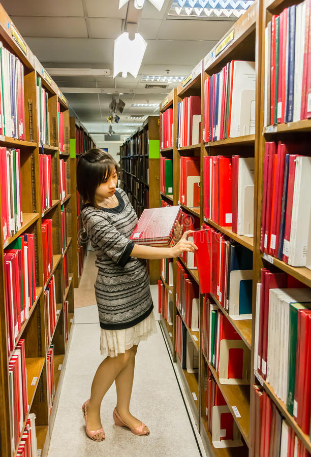 Thai college girl is selecting book from the shelf royalty free stock image