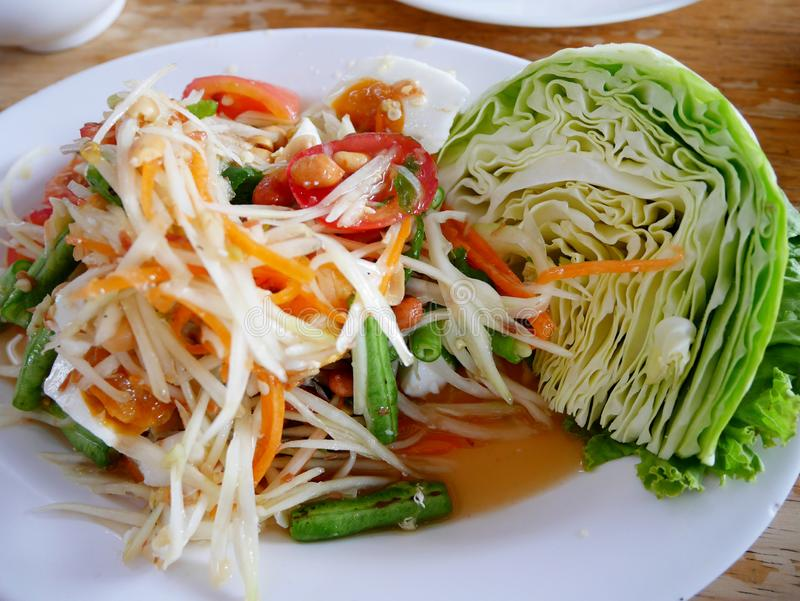 Thai cuisine Somtum or thai food fruit spicy green papaya salad with salted egg on dish serve with cabbage fresh vegetable on dish stock images