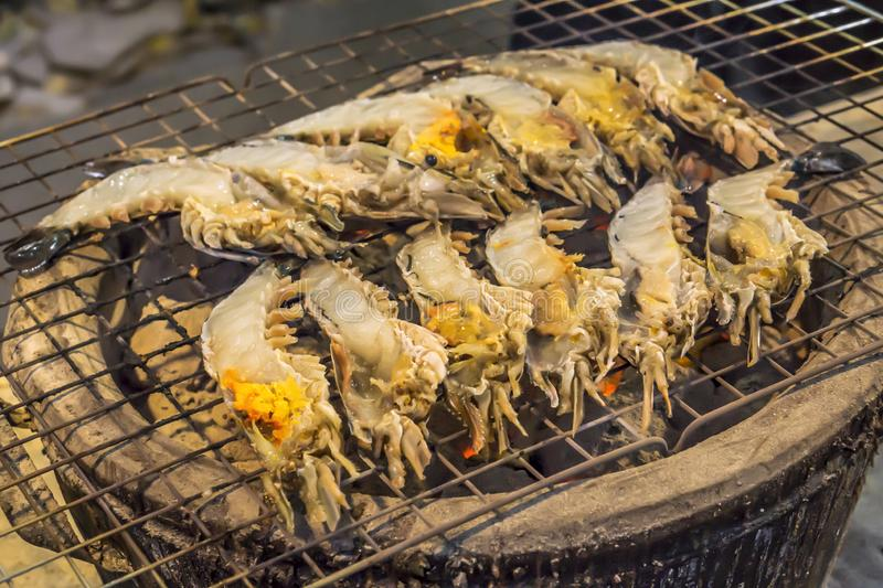 Thai cuisine style, Grilled giant river shrimp. Thai cuisine style, Grilled fresh river shrimp or prawn on the charcoal stove, cutting half and burn served with royalty free stock photos