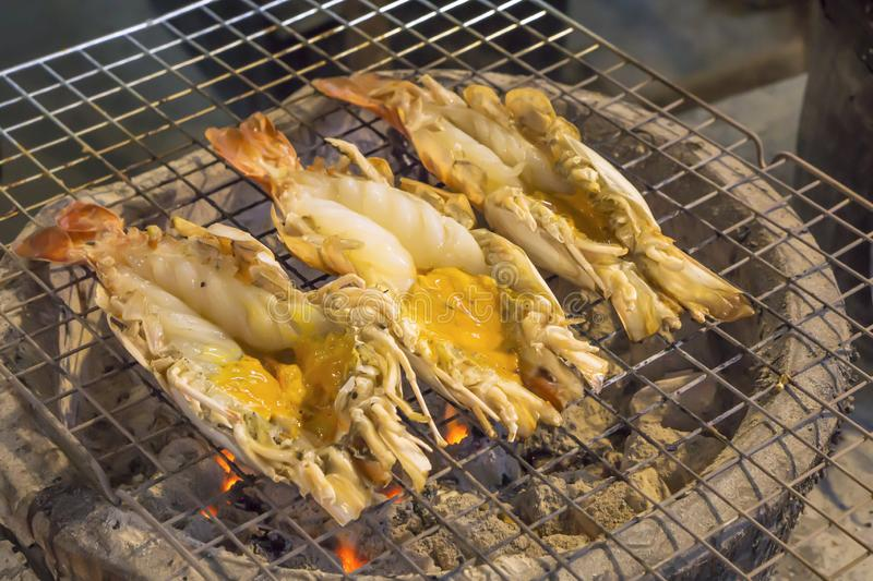 Thai cuisine style, Grilled giant river shrimp. Thai cuisine style, Grilled fresh giant river shrimp or prawn on the charcoal stove, cutting half and burn served royalty free stock image