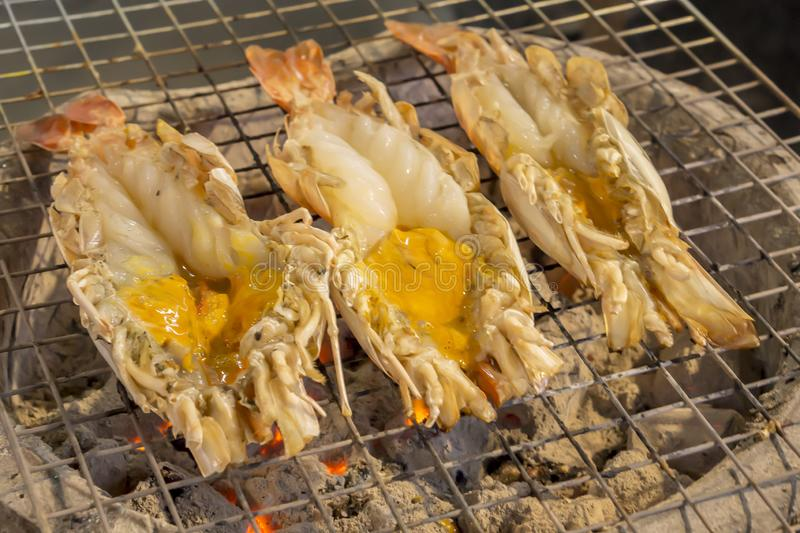 Thai cuisine style, Grilled giant river shrimp. Thai cuisine style, Grilled fresh giant river shrimp or prawn on the charcoal stove, cutting half and burn served stock image