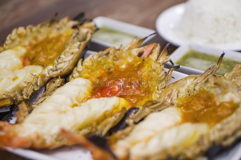 Thai cuisine style, Grilled giant river shrimp. Thai cuisine style, Grilled fresh giant river shrimp or prawn, cutting half and burn served with rice and Thai royalty free stock photography