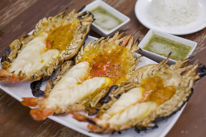 Thai cuisine style, Grilled giant river shrimp. Thai cuisine style, Grilled fresh giant river shrimp or prawn, cutting half and burn served with rice and Thai royalty free stock image