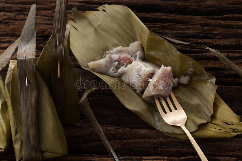 Thai dessert banana leaf tasty on wooden background. Still life rustic close up stock photo